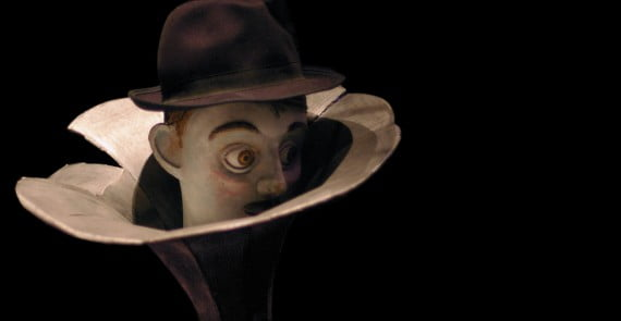 Image of Male puppet poking his head out of the end of a trumpet.